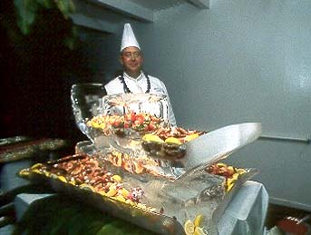 Our chef, posing with a magnificent ice sculpture and luscious tropical fruit. Copyright Milton Fullman