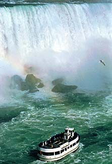 Courtesy of Ontario Tourism. A seagull, boat and rainbow dance on the mists of majestic Niagra Falls.