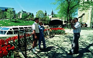 Courtesy of Ontario Tourism. Tourists stop to take photos along Ottawa's scenic Rideau Canal.