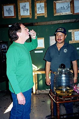 Willing to try anything, Paul Ross samples a supposedly therapeutic sip of rattlesnake sotol. Copyright: Kathryn Means.