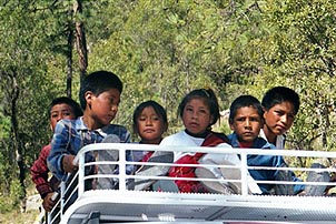 Children in a remote Mexican village catch a ride to school atop a van. Copyright: Kathryn Means.