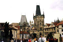 Tourists flock over the Charles Bridge, past its statues of saints and heroes, on their way from the Old Town to the castle. Copyright Kathryn Means.