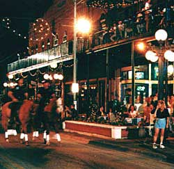 Daytime shoppers give way to partygoers and ghost of the past at night along Seventh Avenue. Copyright Ybor City Chamber of Commerce.